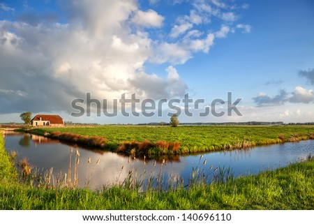 beautiful clouds over charming farmhouse and blue river - stock photo