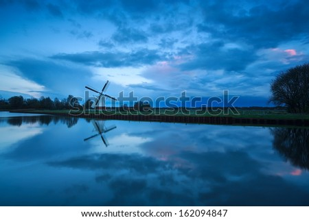 beautiful cloudscape over windmill and river, Holland