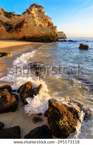 Beautiful coast with cliffs, sand, a wave and the clear blue sky in the warm morning sunlight - stock photo