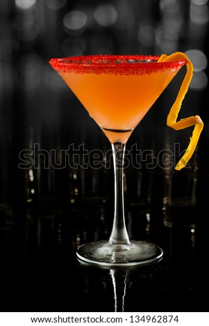 beautiful cocktail served on a dark bar garnished with an orange twist and a sugar rim - stock photo