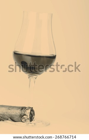 Beautiful cognac or rum with cuban cigar on white background - stock photo