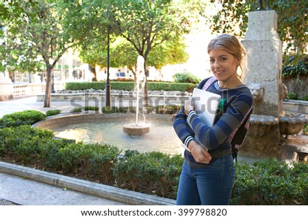 Beautiful college student adolescent girl smiling looking at camera, carrying a laptop computer walking by water fountain in sunny city park, outdoors. Teenager with technology, university lifestyle. - stock photo