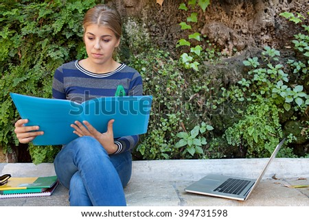 Beautiful college student adolescent girl thoughtful using a laptop computer to study sitting on a stone bench in a park with green foliage background, outdoors. Teenager using technology, lifestyle. - stock photo