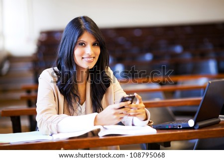 beautiful college student in lecture hall with mobile phone sending sms - stock photo