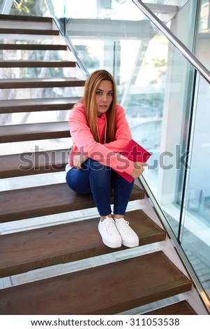 Beautiful college student sitting on the campus with her copybook while resting after classes, clever teenager girl enjoying leisure after class while sitting at the university hallway indoors resting - stock photo