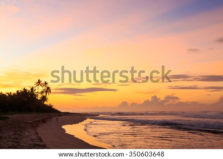 Beautiful colored sunrise at the beach in the tropics - stock photo