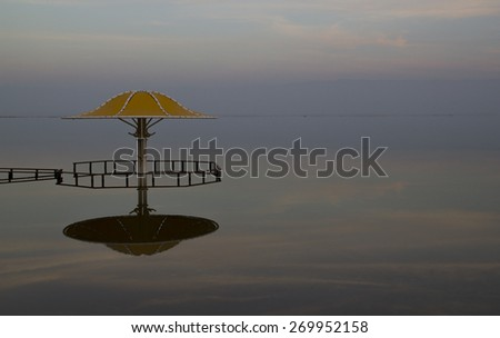 Beautiful Colored Sunset on the Dead Sea - scenery landscape with Yellow Umbrella and Reflection, Israel - stock photo
