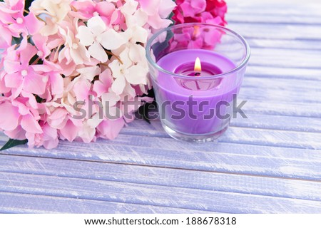 Beautiful colorful candles and flower,on color wooden background - stock photo