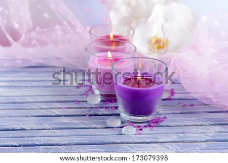 Beautiful colorful candles and  orchid flowers, on color wooden table, on light background - stock photo
