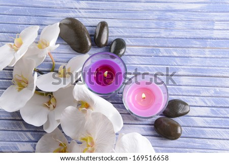 Beautiful colorful candles, spa stones and  orchid flower,on color wooden background - stock photo