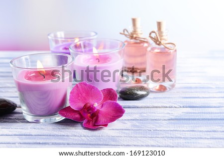Beautiful colorful candles, spa stones and  orchid flower,on color wooden table, on light background - stock photo