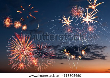 Beautiful colorful holiday fireworks in the evening sky with moon,  long exposure - stock photo