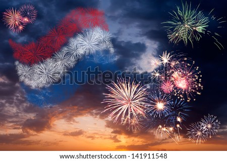 Beautiful colorful holiday fireworks with national flag of Netherlands, evening sky with majestic clouds