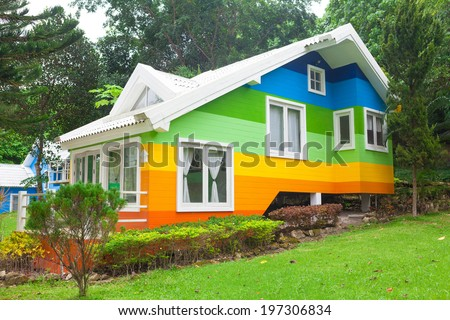 Beautiful colorful house and big tree in forest - stock photo
