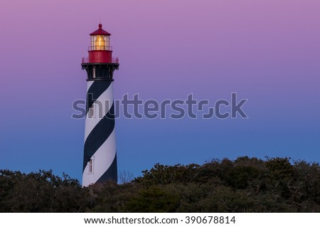 Beautiful colorful Lighthouse along Atlantic Ocean coast close up fresnel lens lighting navigation for ships at sea in Florida