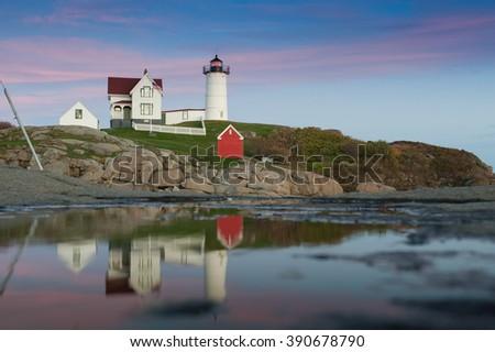 Beautiful colorful Lighthouse along Atlantic Ocean coast in New England marking lighting rocky shore - stock photo