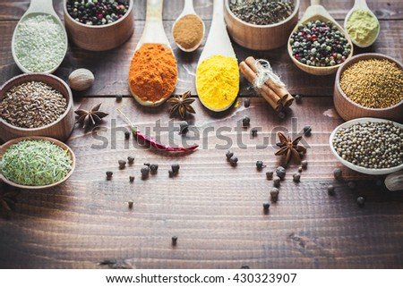 Beautiful colorful spices in spoons on an old wooden brown table. Free space for your text