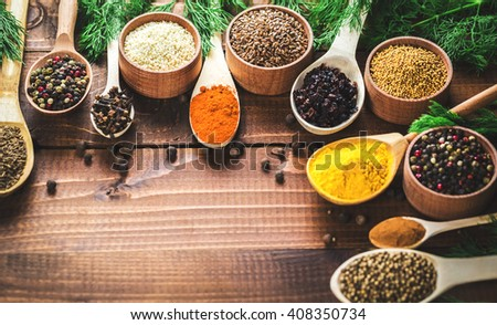 Beautiful colorful spices in wooden spoons and bowls on an old brown table and fresh green dill. Free space for your text