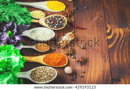 Beautiful colorful spices in wooden spoons and bowls with lettuce, dill and Basil on an old brown table. Free space for your text