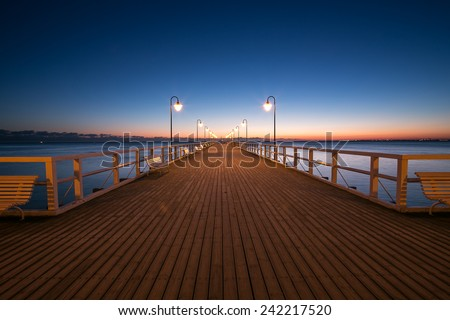 Beautiful colorful Sunrise on the pier at the seaside, Gdynia Orlowo, Poland. Long exposure photography. HDR photo  - stock photo