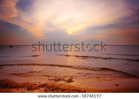 Beautiful colorful sunset over water. - stock photo