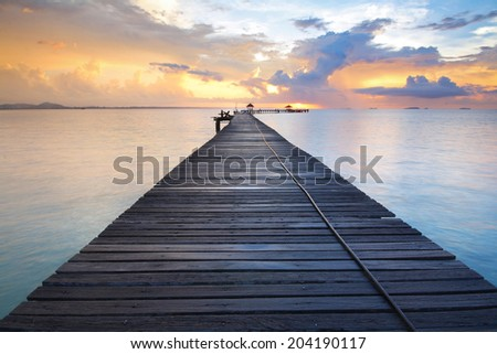 Beautiful colors of the sky and clouds during sunrise and The silhouette of the bridge at Rayong Resort.,Rayong province in Thailand