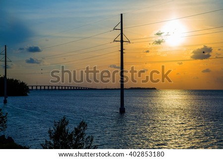 Beautiful colourful sunset or sunrise with bridge leading to Key West and electrical wires next to it  - stock photo