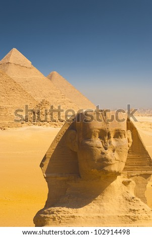 Beautiful composite of all the Giza pyramids behind a close-up of the head of the Great Sphinx on a clear sunny, blue sky day in Cairo, Egypt. Vertical copy space - stock photo