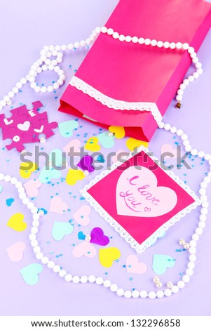 Beautiful composition of paper valentines and decorations on purple background close-up - stock photo