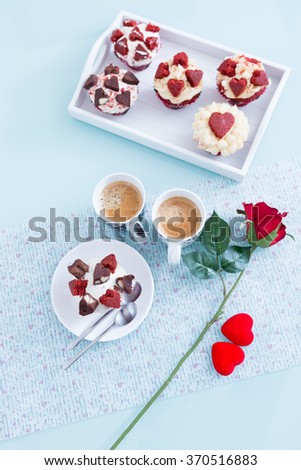 Beautiful composition of Valentines breakfast with handmade cupcakes, coffee and red rose on table. From above.