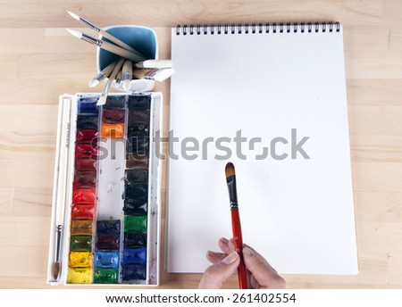 Beautiful composition of watercolor paints, brushes, album artist, with the artist's hand. - stock photo