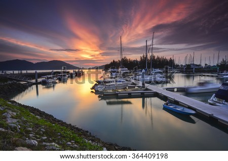 Beautiful composition view of Malaysian Harbour with a yatch during sunset. Noise slighty appear and soft focus due to long exposure - stock photo