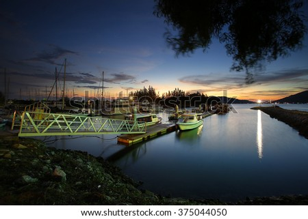 Beautiful composition view of Malaysian Harbour with a yatch during sunset.Vibrance colour,motion blur effect,soft focus due long exposure - stock photo