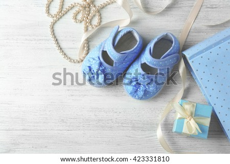 Beautiful composition with baby booties and gift box on wooden background - stock photo