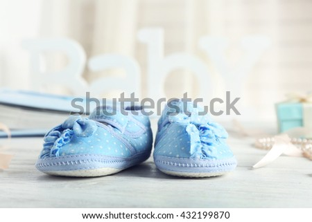 Beautiful composition with baby booties on wooden background - stock photo