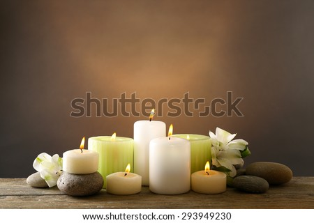 Beautiful composition with candles and spa stones on dark background - stock photo