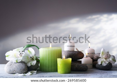 Beautiful composition with candles and spa stones on light background - stock photo