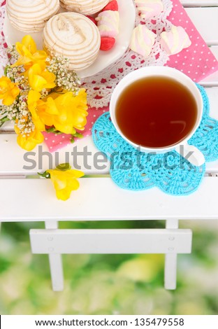 Beautiful composition with cup of tea and marshmallow on wooden picnic table close-up - stock photo