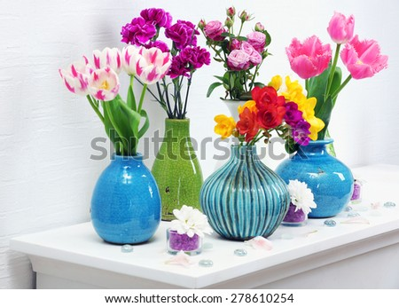 Beautiful composition with different flowers in vases on wall background - stock photo