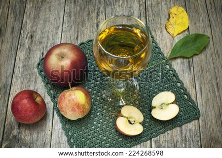 Beautiful composition with juice in a glass, apples and fallen leaves on old wooden background. Grunge style. Delicious fruit. Image of natural materials.  - stock photo