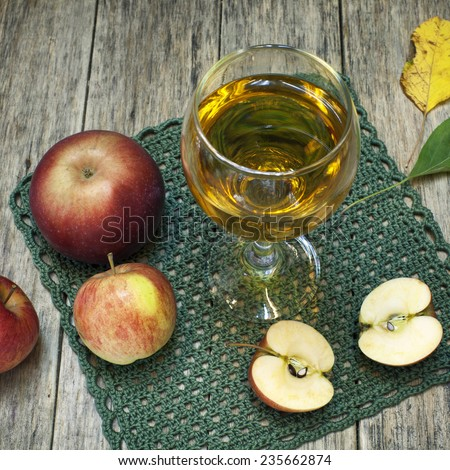 Beautiful composition with juice in a glass, apples and fallen leaves on old wooden background. Grunge style. Delicious fruit. Square image of natural materials. - stock photo