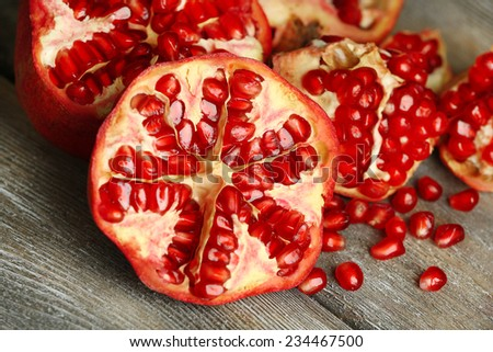 Beautiful composition with juicy  pomegranates, on old wooden table - stock photo