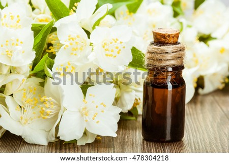 Beautiful compositions of fresh jasmine flowers and a small glass bottle of essential oil on wooden table - aroma and skincare concept