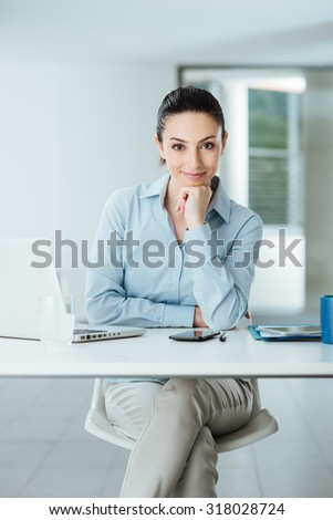 Beautiful confident female manager sitting at office desk and smiling at camera with hand on chin, room interior on background - stock photo