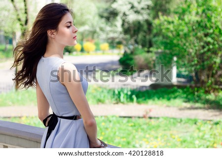 Beautiful confident girl standing on palace balcony on sunny day. Wind blows her hair