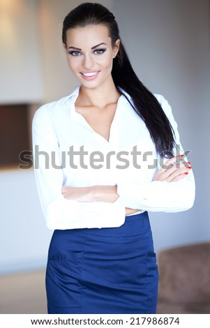 Beautiful confident woman with a charming smile standing with her arms folded looking at the camera as she stands indoors at home - stock photo