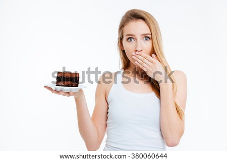 Beautiful confused young woman on diet holding piece of chocolate cake over white background - stock photo