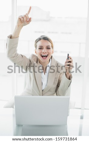 Beautiful content businesswoman sitting on her swivel chair cheering looking at camera - stock photo