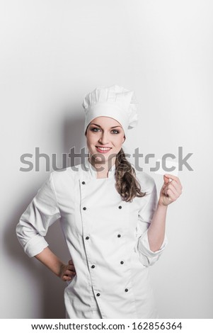 Beautiful cook woman holding blank card over a white background - stock photo
