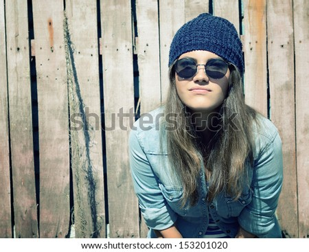 beautiful cool girl in hat and sunglasses against grunge wooden fence, toned - stock photo
